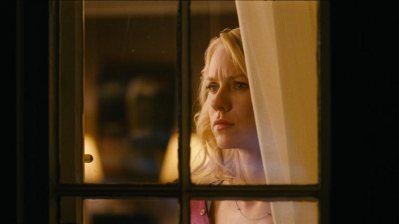 Naomi Watts sospettosa dietro una finestra in una scena di Dream House