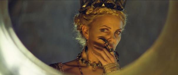 Charlize Theron si osserva nello specchio magico in una scena de Biancaneve e il cacciatore