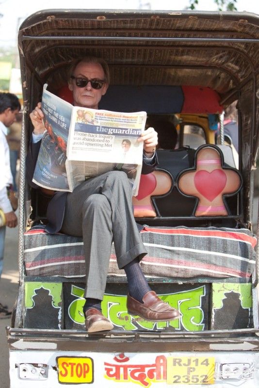 Marigold Hotel: Bill Nighy in una scena del film legge The Guardian a bordo dei una carrozzella indiana