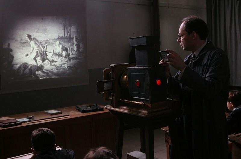Denis Podalydès, nei panni del maestro Bernard, proietta un film in classe in una scena de Il primo uomo