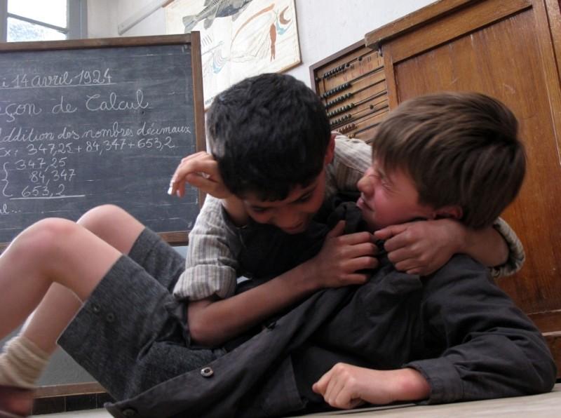 Nino Jouglet si azzuffa con un compagno di classe in una scena de Il primo uomo