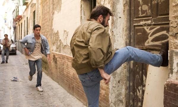 Antonio De La Torre sfonda una porta a calci in Grupo 7. Dietro di lui, Mario Casas