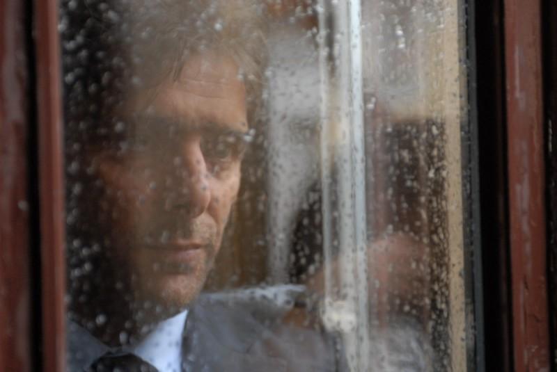 Sandrine nella pioggia: Adriano Giannini guarda la pioggia in una scena del film
