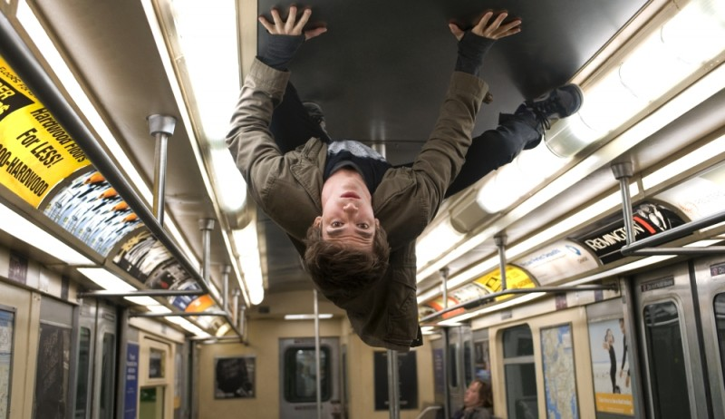 Andrew Garfield cammina a testa in giu sul tetto di un autobus in una scena The Amazing Spider-Man