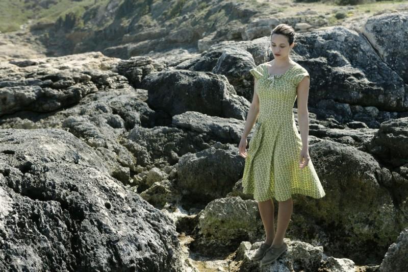 Isole: Asia Argento passeggia sugli scogli in una scena del film