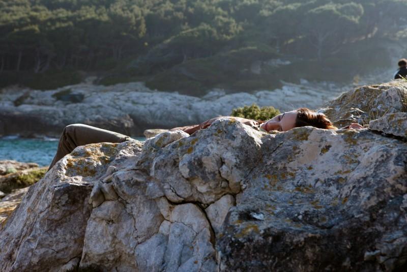 Isole: Asia Argento sdraiata sulle rocce in una scena del film