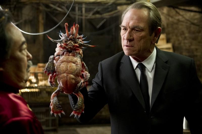 Men in Black 3: Tommy Lee Jones con un mostriciattolo alieno in mano in una scena del film