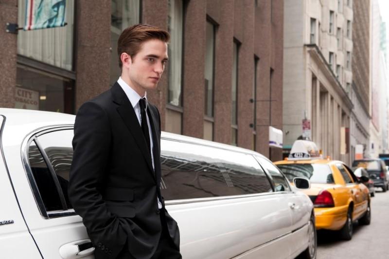 Cosmopolis: Robert Pattinson in una scena del film poggiato su una lunghissima limousine