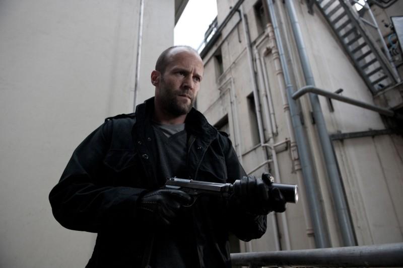 Killer Elite: Jason Statham con la sua arma letale in una scena del film