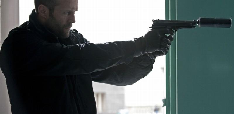 Killer Elite: Jason Statham punta la sua arma in una scena dell'action movie