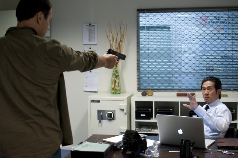 Bait: Julian McMahon (di spalle) in una scena del film minaccia Adrian Pang con una pistola