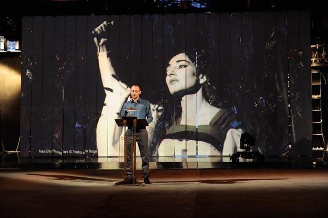 Elio Germano a Quello che (non) ho - dietro di lui, un'immagine di Maria Callas
