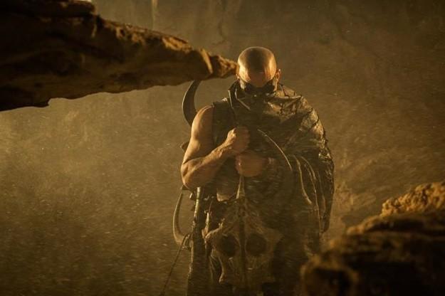 Vin Diesel, camuffato accuratamente, spunta tra le rocce in un'immagine tratta dal set di Riddick