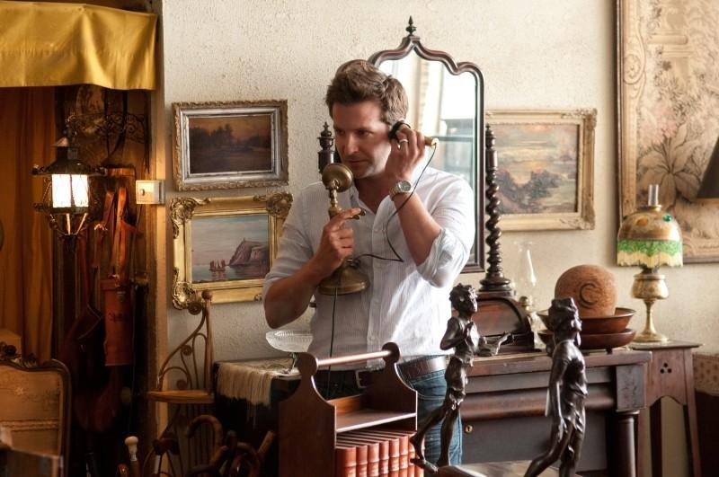 Bradley Cooper alle prese con un vecchio telefono d'antiquariato in una scena di The Words