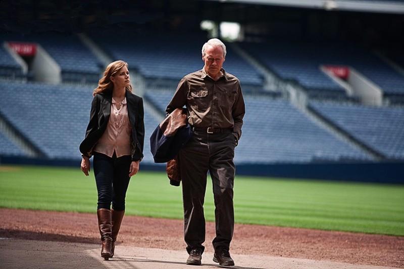 Clint Eastwood ed Amy Adams camminano in un campo di football in una scena di The Trouble with the Curve