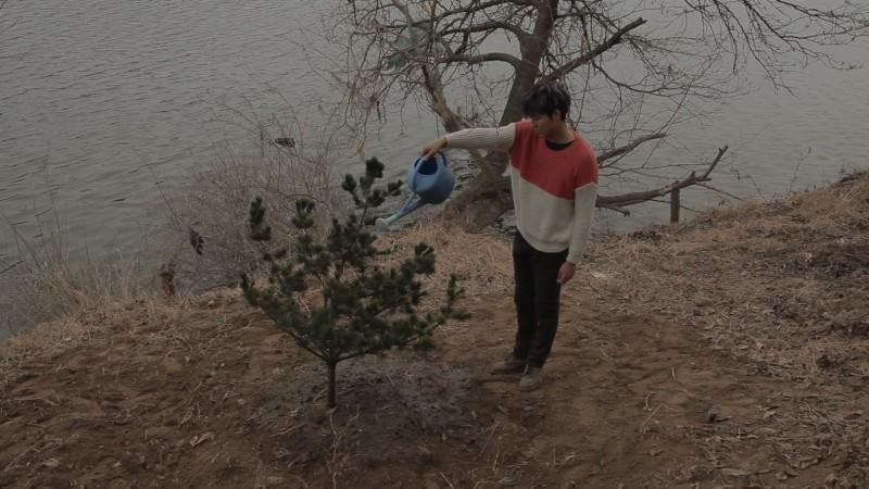 Pietà: Lee Jung-jin innaffia un albero in riva al fiume in una scena del dramma di Kim Ki-duk