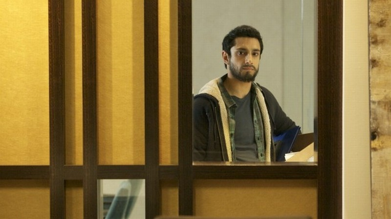 Riz Ahmed guarda fuori dalla finesta in una scena di The Reluctant Fundamentalist