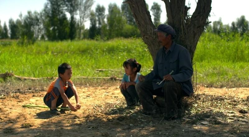 Fly with the Crane: l'anziano Ma Xingehun in una scena del film con alcuni bambini