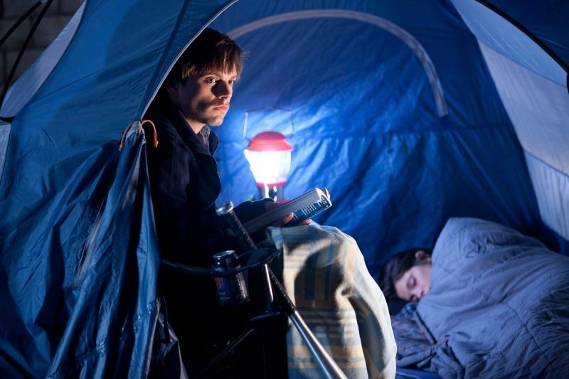 Sebastian Stan si rifugia in una tenda, con tanto di lanterna accesa, nel film The Apparition