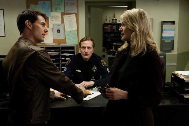 Tom Cruise e Rosamund Pike di fronte a un poliziotto in una scena di Jack Reacher - La prova decisiva