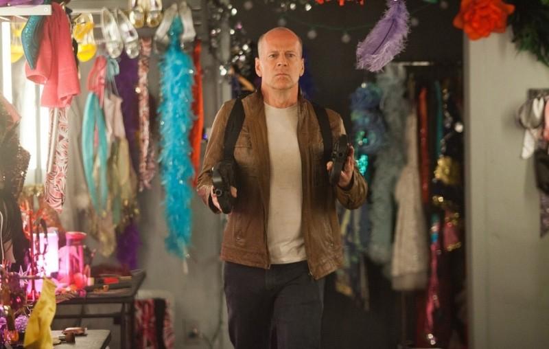 Bruce Willis imbraccia due mitra in una scena di Looper