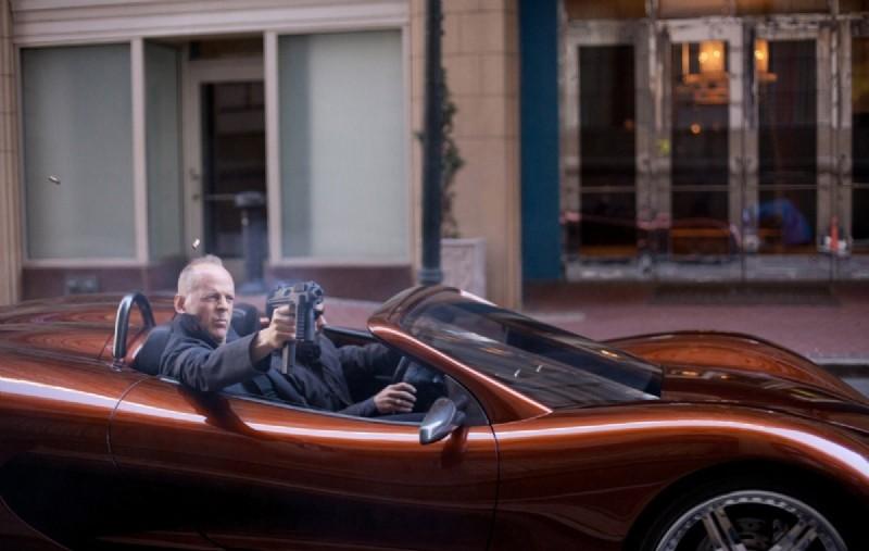 Bruce Willis spara dalla sua decapottabile in una concitata sequenza di Looper