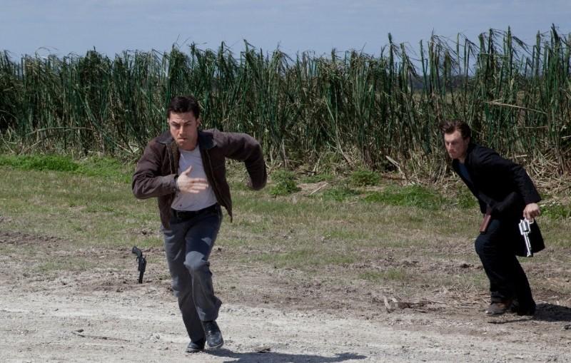 Joseph Gordon-Levitt tenta la fuga, inseguito da Noah Segan, in una scena di Looper