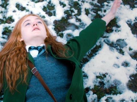 Elle Fanning sdraiata nella neve in un'immagine di Ginger & Rosa