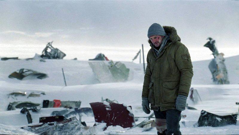 Liam Neeson distrutto di fronte al relitto del suo aereo in una scena di The Grey