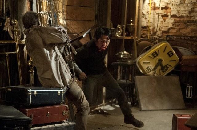 The Walking Dead: Steven Yeun alle prese con un Errante in una scena dell'episodio Infiltrati