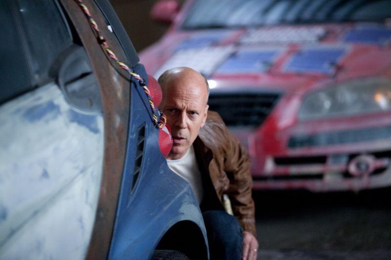 Bruce Willis appostato dietro un'auto in una scena di Looper