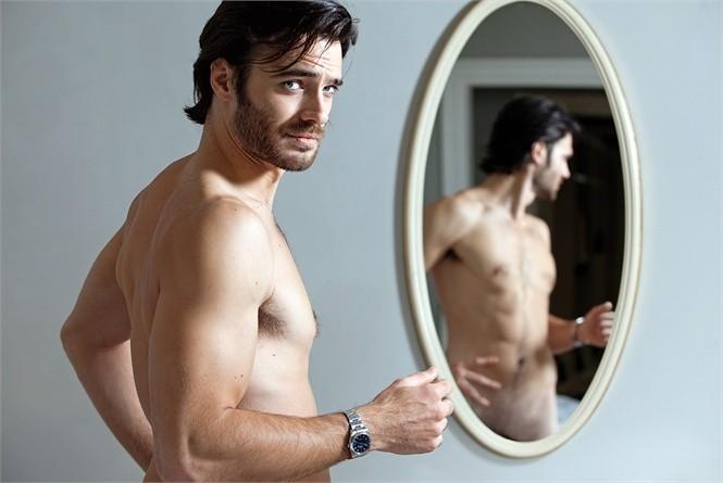 Giulio Berruti a torso nudo davanti allo specchio.