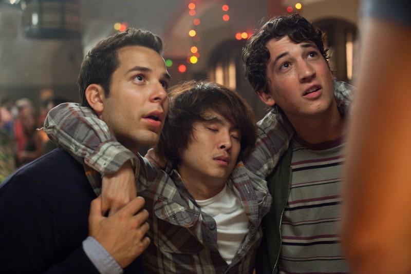 Miles Teller e Skylar Astin sorreggono Justin Chon in una scena di Un compleanno da leoni