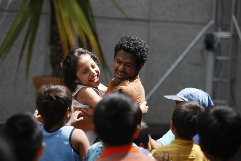 Jamel Debbouze sorride insieme a tanti bambini in una scena di Marsupilami