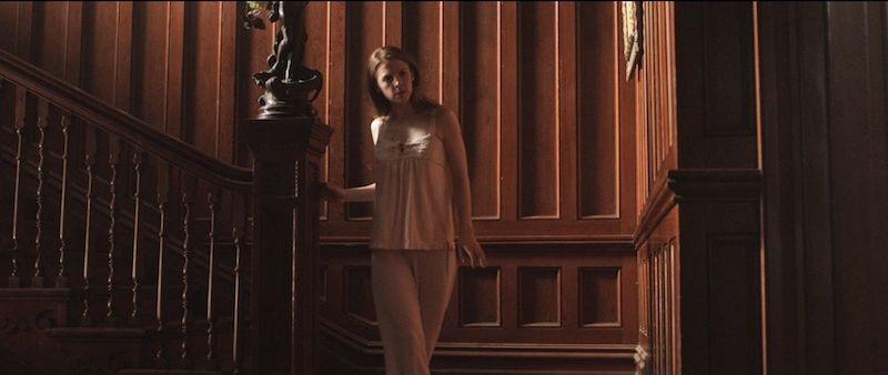 The Last Exorcism 2: Ashley Bell si aggira per la casa in maniera sospettosa in una scena del film