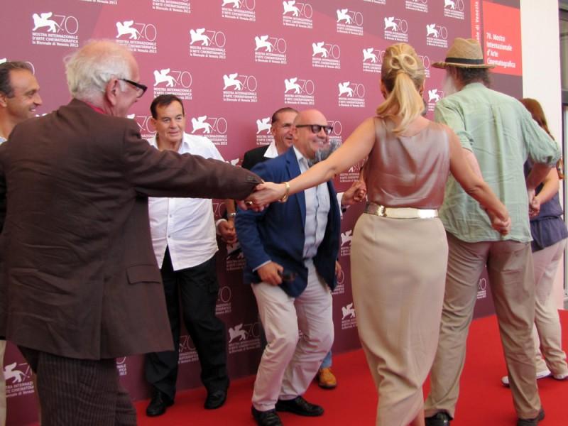 Sacro GRA a Venezia 2013 il regista Gianfranco Rosi al centro di un girotondo con il suo cast