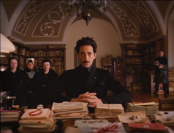 The Grand Budapest Hotel: un minaccioso Adrien Brody con alle spalle le tre sorelle