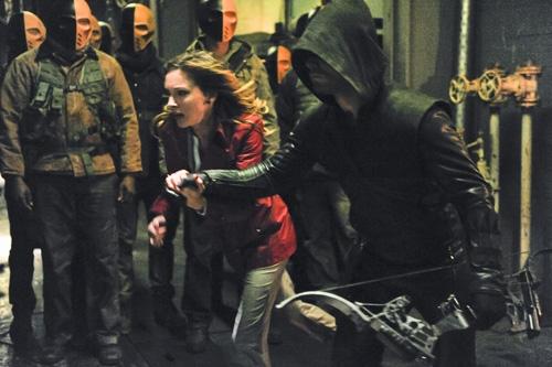 Arrow: Stephen Amell in fuga con Katie Cassidy in una scena dell'episodio City of Blood, seconda stagione