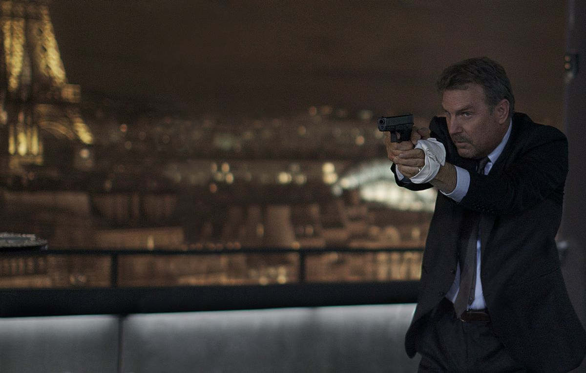 3 Days to Kill: Kevin Costner in una scena d'azione del film punta la sua pistola