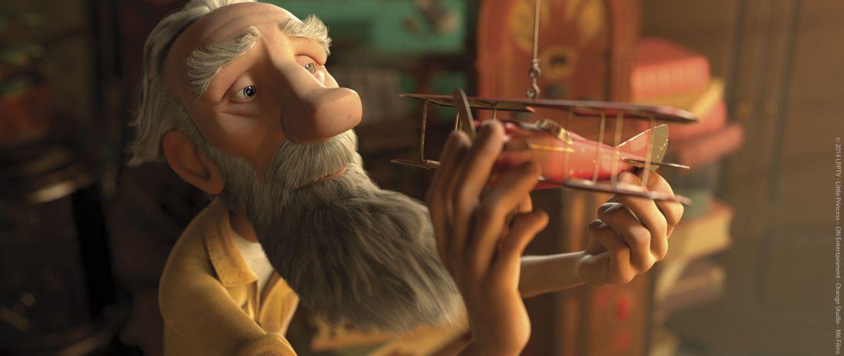 Il Piccolo Principe: l'aviatore con un modellino di aereo viaggia nei ricordi in un momento del film d'animazione