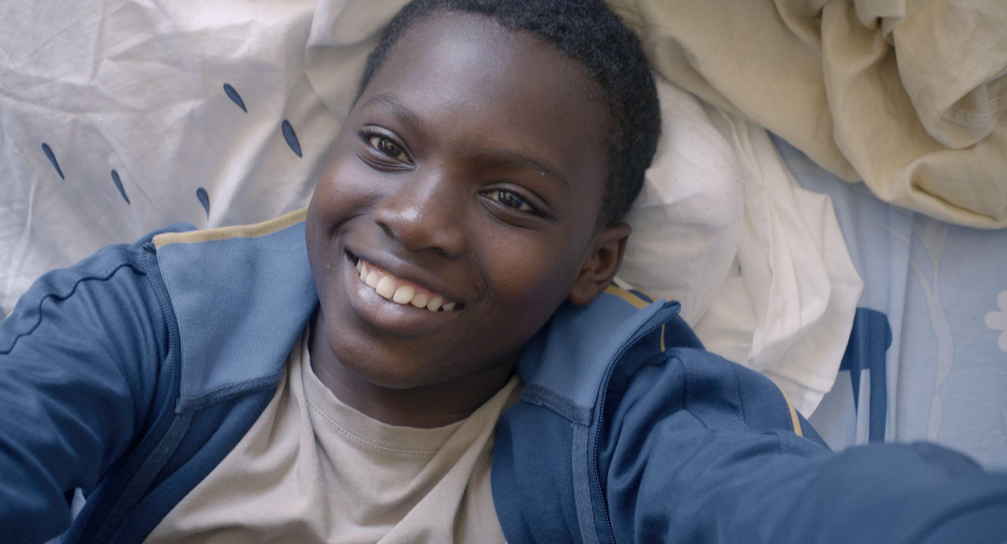 La vie en grand: Balamine Guirassy in un primo piano sorridente tratto dal film