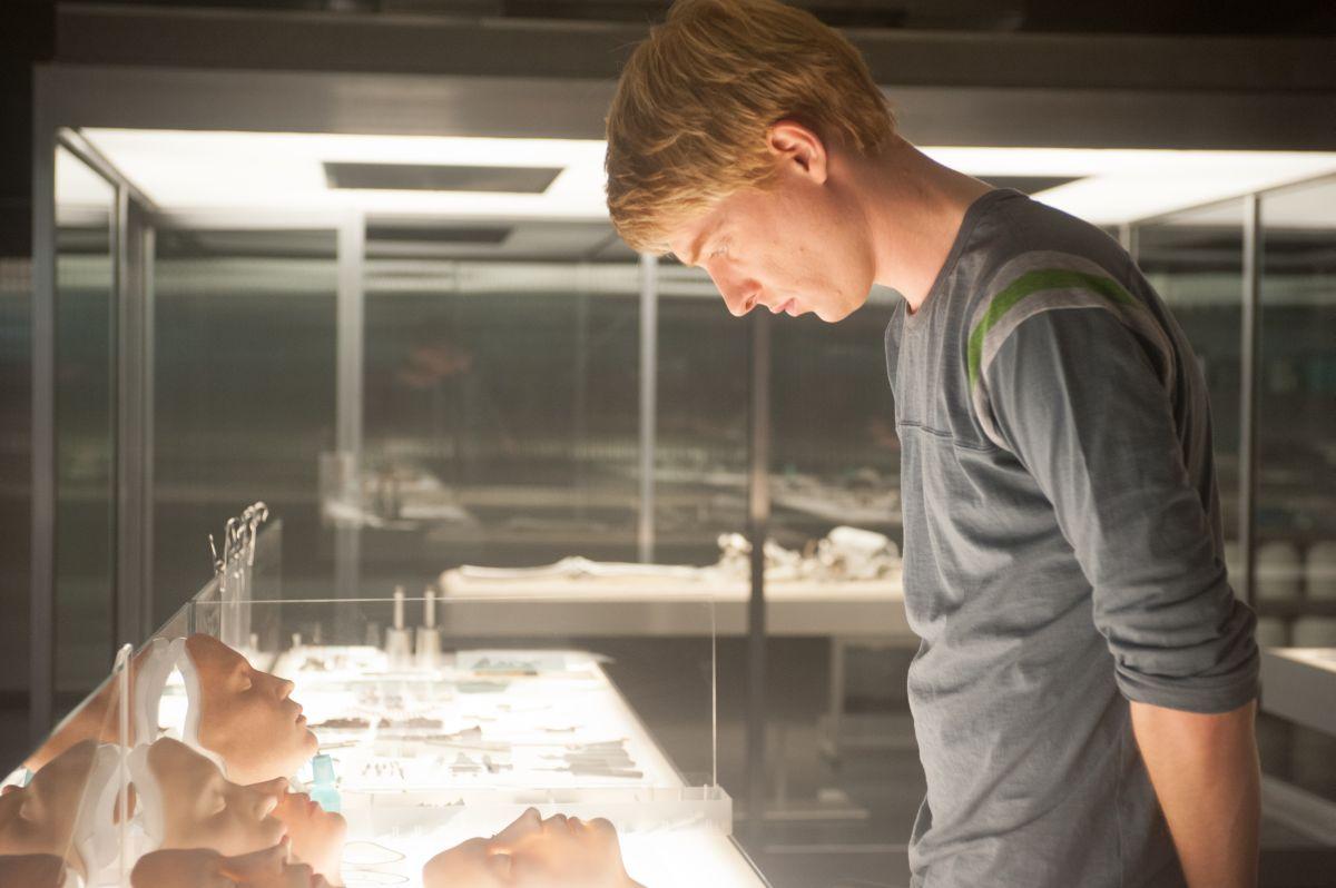 Ex Machina: Domhnall Gleeson osserva le facce dei robot in una scena del film