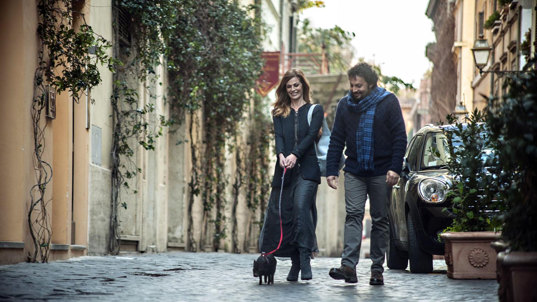 Tutte lo vogliono: Vanessa Incontrada ed Enrico Brignano passeggiano sorridenti in un'immagine del film