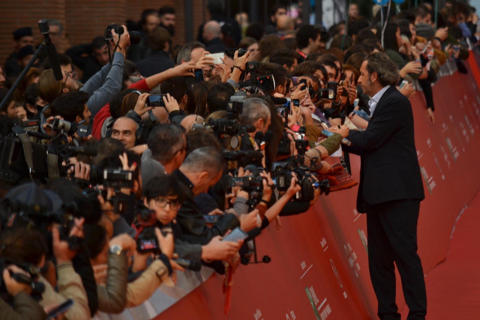 Roma 2015: Paolo Sorrentino mentre firma autografi sul red carpet