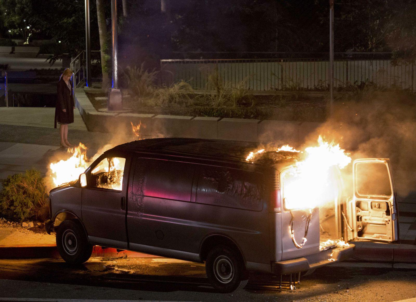 Il segreto dei suoi occhi: una scena del film con un furgone in fiamme e, sullo sfondo, Nicole Kidman