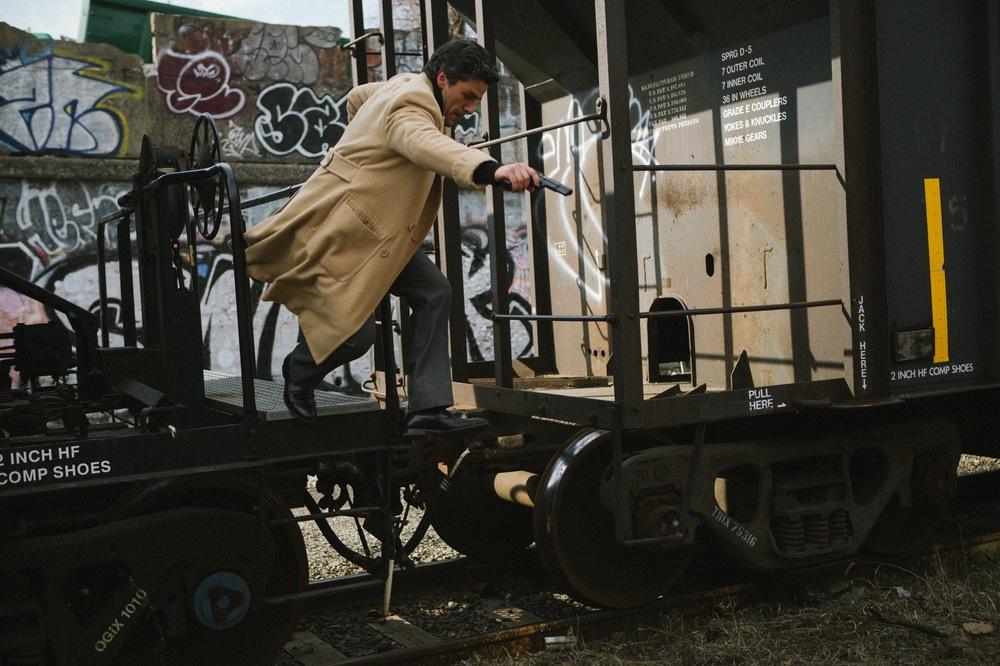1981: Un'indagine a New York, Oscar Isaac con una pistoila in mano in una scena del film