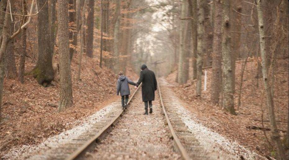 Cell: una scena ambientata nei boschi in cui John Cusack tiene per mano un bambino