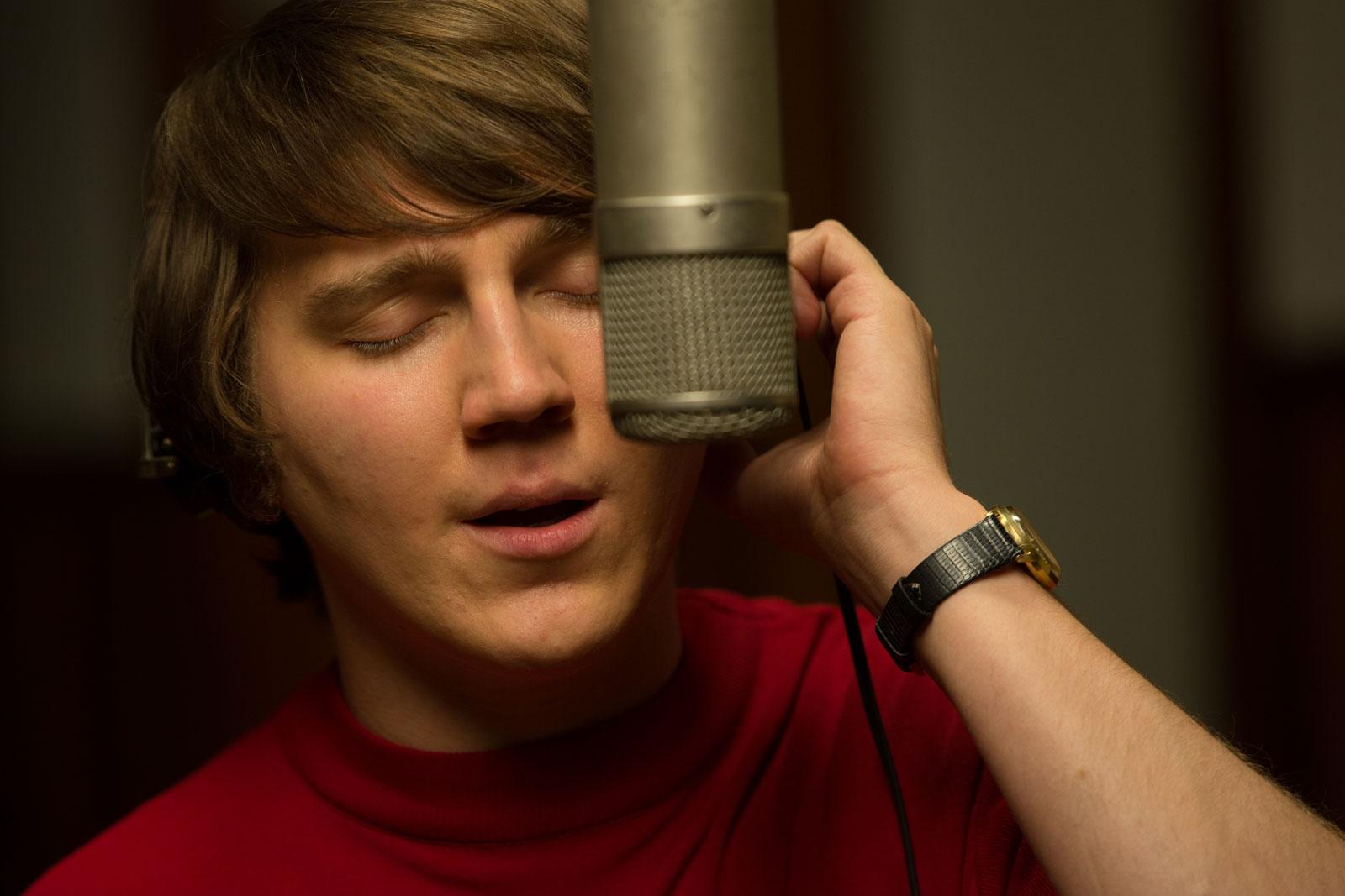 Love & Mercy: un primo piano di Paul Dano impegnato a cantare