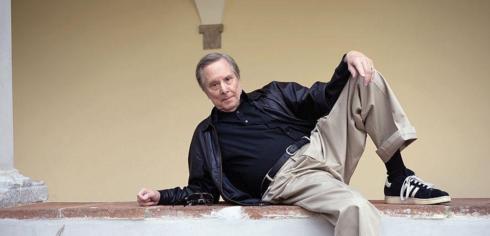 William Friedkin sdraiato su un muretto nel cortile di San Micheletto a Lucca