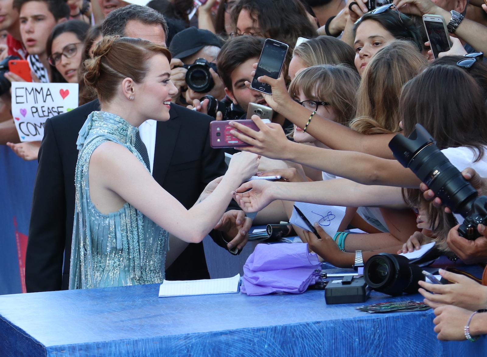 Venezia 2016: Emma Stone firma autografi sul red carpet